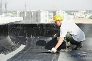 Roofer Installing Sheets of Roof Membrane